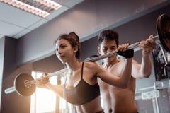 Donne d'aiuto dell'istruttore personale e bilancieri pesanti due Han della maniglia Immagine Stock Libera da Diritti