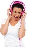 Donne del Brunette chegodono dell'oscillazione con la musica forte Fotografie Stock