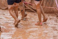 Donne del corridore di corsa del fango che strisciano nel fango nell'ambito degli ostacoli fotografie stock libere da diritti
