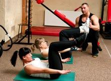 Donne del randello di forma fisica con l'addestratore Fotografia Stock