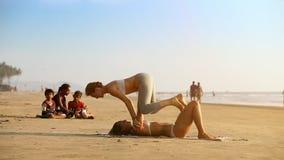 Donne dell'orologio dei bambini che fanno yoga delle coppie sulla spiaggia archivi video