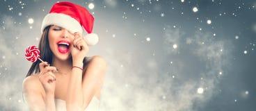 Donne della Santa con i sacchetti Ragazza di modello allegra in cappello di Santa con le labbra e la caramella rosse della lecca- fotografie stock