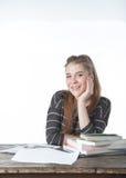 Donne dello studente che si siedono sulla tavola di legno con le sue mani e sulla spalla sui libri Ragazza sorridente con i libri Fotografia Stock Libera da Diritti