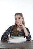 Donne dello studente che si siedono sulla tavola di legno con le sue mani e sulla spalla sui libri Ragazza sorridente con i libri Fotografie Stock Libere da Diritti