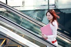 Donne di affari che tengono dispositivo di piegatura sulla scala mobile Immagine Stock Libera da Diritti