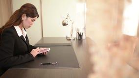 Donne di affari che tengono smartphone moderno e che toccano su uno schermo archivi video