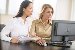 Donne di affari che usando desktop pc fotografie stock