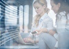 Donne di affari con il telefono ed il computer portatile dietro la sovrapposizione grafica della freccia blu Fotografie Stock Libere da Diritti