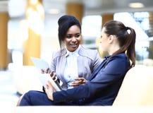 Donne di affari con seduta della compressa di Digital Fotografia Stock Libera da Diritti
