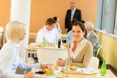 Donne di affari del pranzo del self-service le giovani mangiano l'insalata Immagine Stock