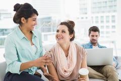 Donne di affari sorridenti che chiacchierano insieme sullo strato Fotografia Stock Libera da Diritti