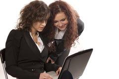 Donne di affari sorridenti con il computer portatile Fotografia Stock