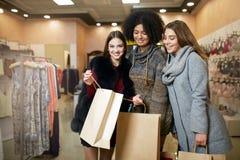 Donne di diversa etnia con i sacchetti della spesa che posano nel negozio di vestiti Un ritratto di tre ragazze multirazziali sor fotografie stock
