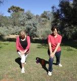 Donne di mezza età che allungano le gambe prima dell'esercizio. fotografia stock libera da diritti