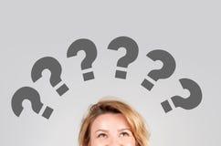 Donne di pensiero con i punti interrogativi sopra la sua testa Fotografia Stock Libera da Diritti