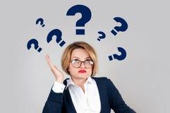 Donne di pensiero con i punti interrogativi su fondo bianco Fotografia Stock