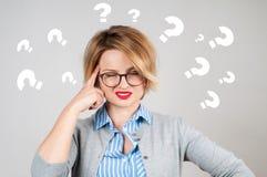 Donne di pensiero con i punti interrogativi su fondo bianco Immagini Stock