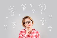 Donne di pensiero con i punti interrogativi su fondo bianco Fotografie Stock Libere da Diritti