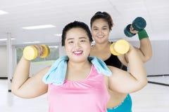 Donne di peso eccessivo che si esercitano con le teste di legno Immagine Stock