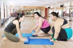 Donne di peso eccessivo e la loro stuoia di scorrimento dell'istruttore Fotografia Stock Libera da Diritti