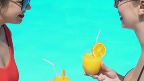 Donne di risata in vetri di cocktail tintinnanti della piscina, evento di celebrazione stock footage