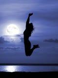 Donne di salto della siluetta sulla notte della luna Immagine Stock Libera da Diritti