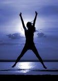 Donne di salto della siluetta sulla notte della luna Immagini Stock