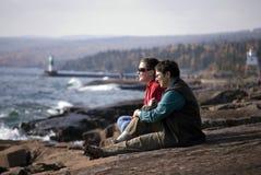 donne di seduta vicine del lago Fotografia Stock
