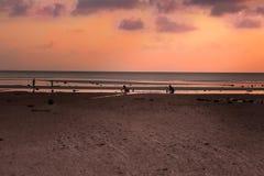Donne e bambini che cercano le coperture nel mare durante il tramonto immagine stock