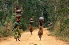 Donne e bambini che trasportano i POT nel Burundi. Immagini Stock