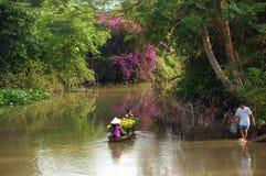 Donne e bambini sulla barca a remi con il forTet del fiore nella primavera Immagini Stock Libere da Diritti