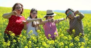 Donne e ragazze che mostrano colpo giù su un campo della colza - delusione stock footage