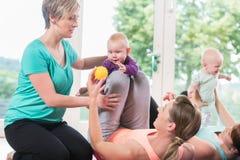 Donne ed i loro bambini nel corso relativo alla ginnastica del madre-bambino fotografia stock libera da diritti