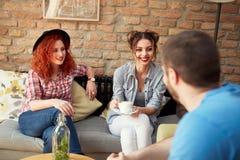 Donne ed uomo sorridenti che chiacchierano con la tazza di caffè Fotografia Stock