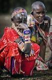 Donne editoriali della tribù di Massai della foto in vacanza nei bei gioielli e vestiti, sedentesi sulla terra nel suo villaggio Immagini Stock Libere da Diritti