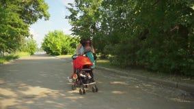 2 donne esaminano il telefono cellulare mentre il bambino dorme nel passeggiatore stock footage