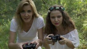 Donne euforiche e disperate felici che giocano i video giochi della concorrenza della console nella foresta - archivi video