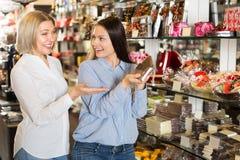 Donne felici che comprano le barre di cioccolato Fotografia Stock