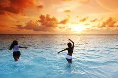 Donne felici che giocano in acqua fotografie stock libere da diritti