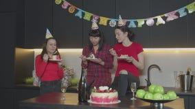 Donne felici che mangiano torta di compleanno in cucina domestica archivi video