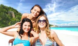 Donne felici che prendono il sole sulle sedie alla spiaggia di estate Immagine Stock Libera da Diritti