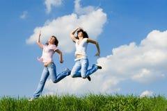 Donne felici che saltano sull'erba verde Fotografia Stock