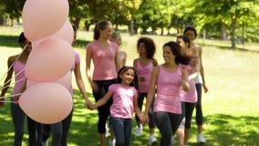 Donne felici che vanno su una passeggiata per consapevolezza del cancro al seno nel parco stock footage