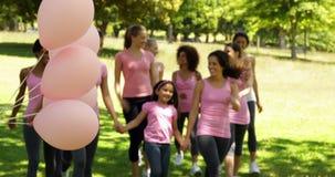 Donne felici che vanno su una passeggiata per consapevolezza del cancro al seno nel parco video d archivio