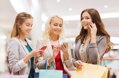 Donne felici con gli smartphones ed i sacchetti della spesa Immagini Stock