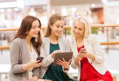 Donne felici con gli smartphones ed il pc della compressa in centro commerciale Immagine Stock Libera da Diritti