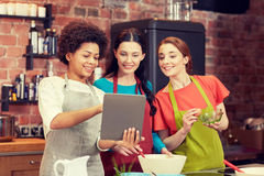 Donne felici con il pc della compressa che cucinano nella cucina Immagine Stock