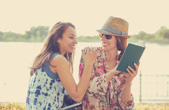 Donne felici degli studenti degli amici che studiano il libro di lettura all'aperto Fotografia Stock