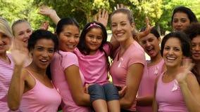 Donne felici nel rosa per consapevolezza del cancro al seno nel parco che ondeggia alla macchina fotografica stock footage