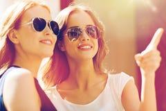 Donne felici in occhiali da sole che indicano dito all'aperto Fotografie Stock Libere da Diritti